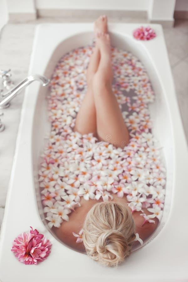 温泉放松 与羽毛热带花的白肤金发的享用的浴 r 有沐浴赤裸的腿的美丽的性感女孩 免版税库存照片