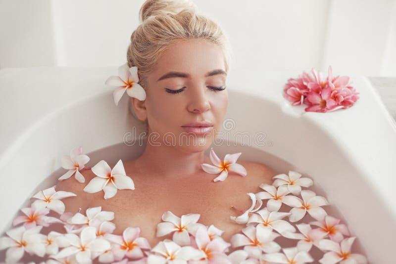 温泉放松 与羽毛热带花的白肤金发的享用的浴 r 沐浴与瓣的特写镜头美丽的性感女孩 免版税库存照片