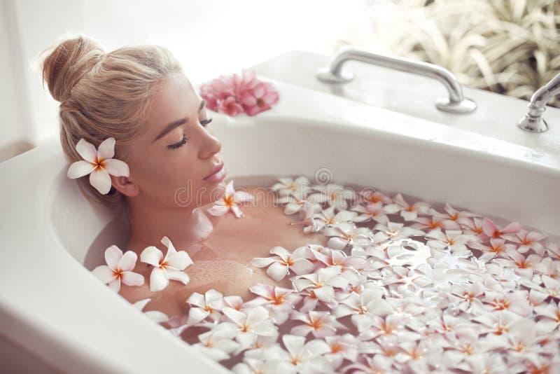 温泉放松 与羽毛热带花的白肤金发的享用的浴 r 沐浴与瓣的特写镜头美丽的性感女孩 库存图片