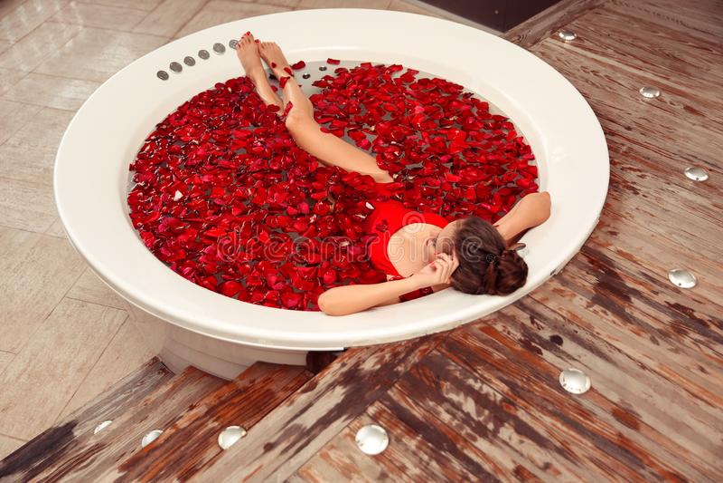 温泉放松 在与红色玫瑰花瓣的圆的极可意浴缸的美丽的比基尼泳装妇女 r 红色游泳衣的性感女孩 免版税图库摄影