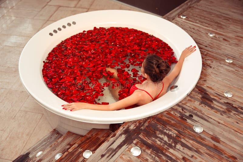 温泉放松 极可意浴缸的美女 在与红色玫瑰花瓣的圆的浴的比基尼泳装妇女 r 红色的性感女孩 库存图片