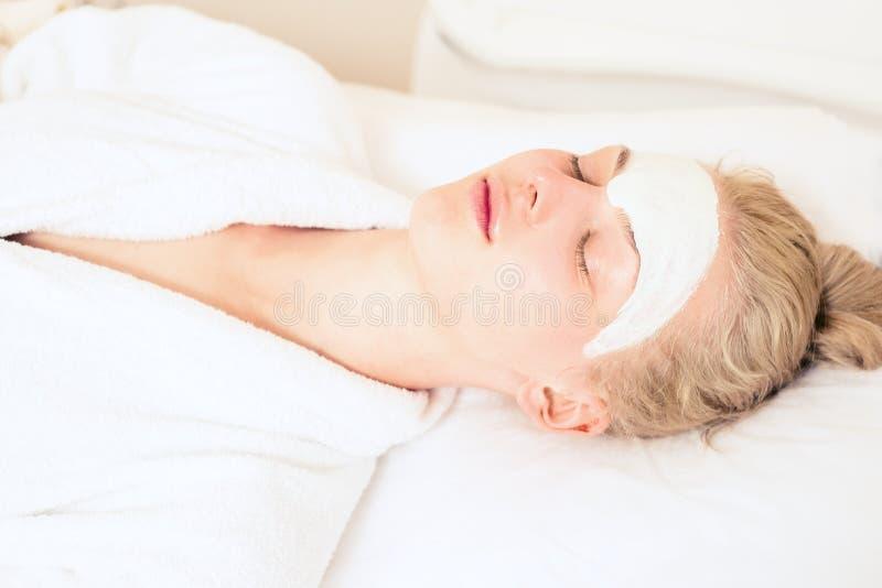 温泉整容术 女孩患者是在清洗的皮肤方法 在妇女的面孔,应用清洁剂 Cicep 库存图片