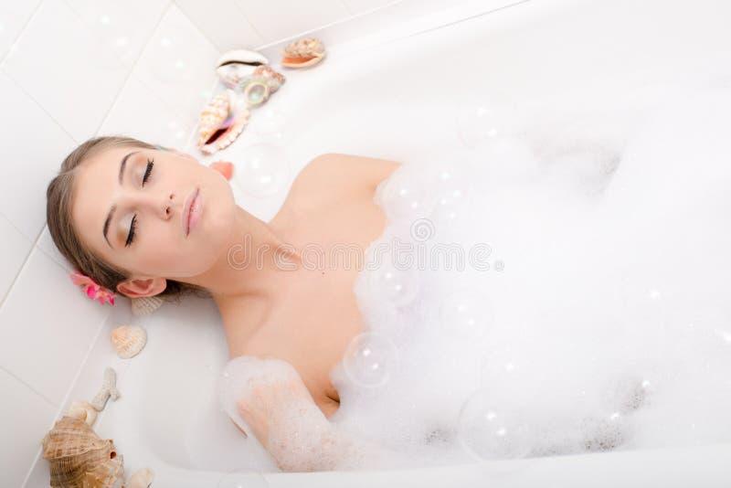 温泉时间:美丽的典雅的夫人放松的在有泡沫的一个浴缸与眼睛关闭了画象 免版税库存图片