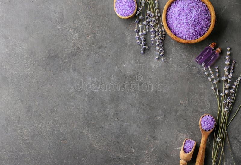 温泉构成用美丽的淡紫色和海盐在黑暗的桌上 库存图片