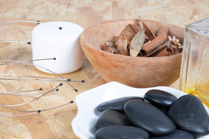 温泉概念禅宗玄武岩黑色石头和瓶油按摩蜡烛在木背景 免版税库存照片