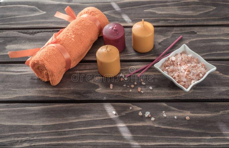 温泉概念 蜡烛、芳香盐和橙色毛巾 免版税库存照片