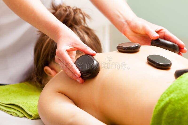 温泉沙龙。放松的妇女有热的石按摩。Bodycare。 免版税库存照片