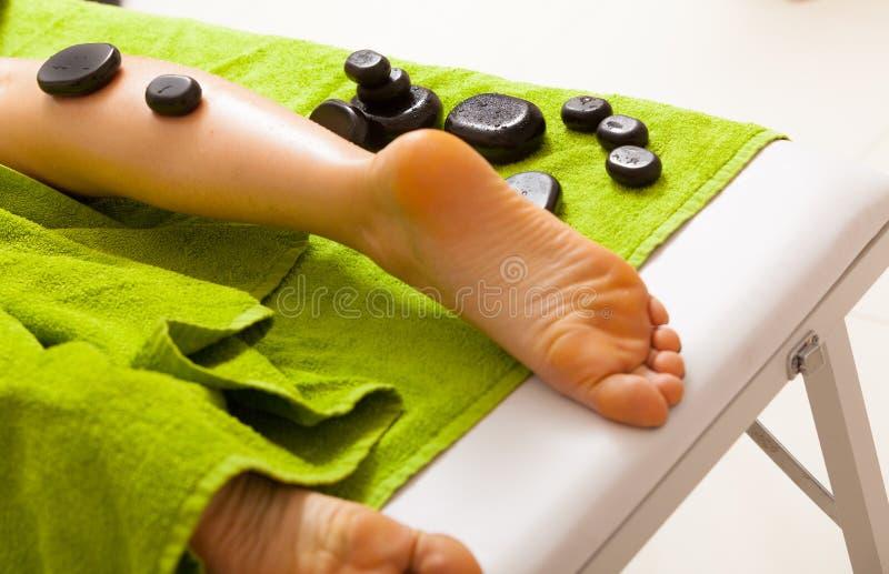 温泉沙龙。有女性的腿热的石按摩。Bodycare和放松。 免版税库存图片
