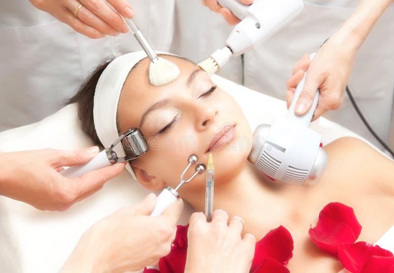 温泉沙龙:有年轻美丽的妇女各种各样的面部治疗 库存图片