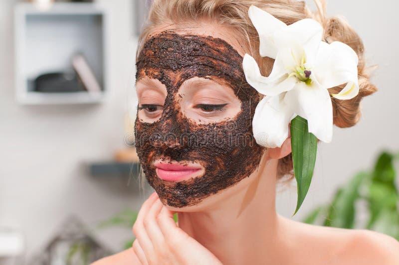 温泉沙龙 有咖啡面部面具的美丽的妇女在美容院 免版税库存照片