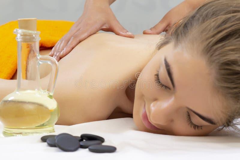 温泉热的石按摩 说谎在温泉沙龙温泉芳香疗法和秀丽治疗概念的按摩床上的可爱的美女 库存照片