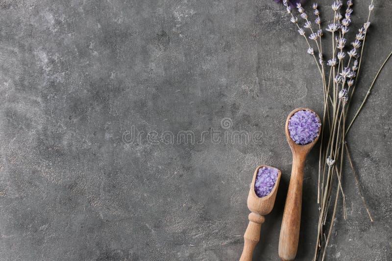 温泉的海盐和在黑暗的桌上的美丽的淡紫色 免版税库存照片