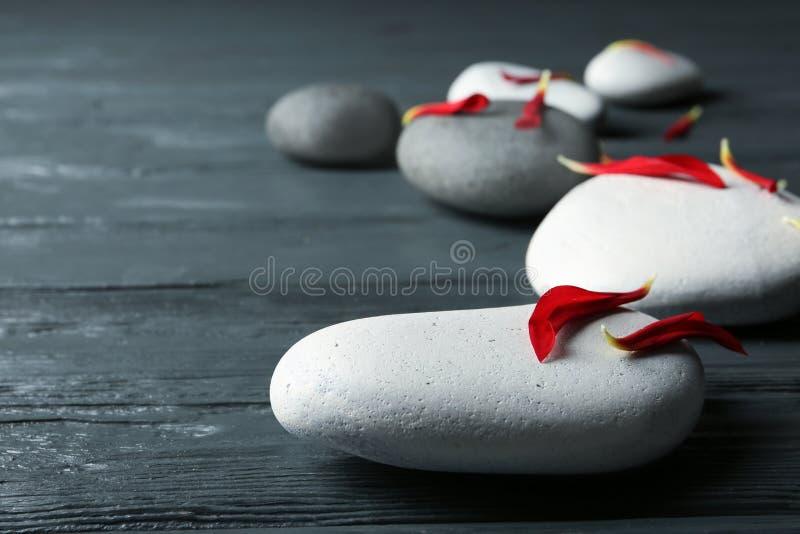 温泉石头和花瓣在木桌上, 免版税图库摄影