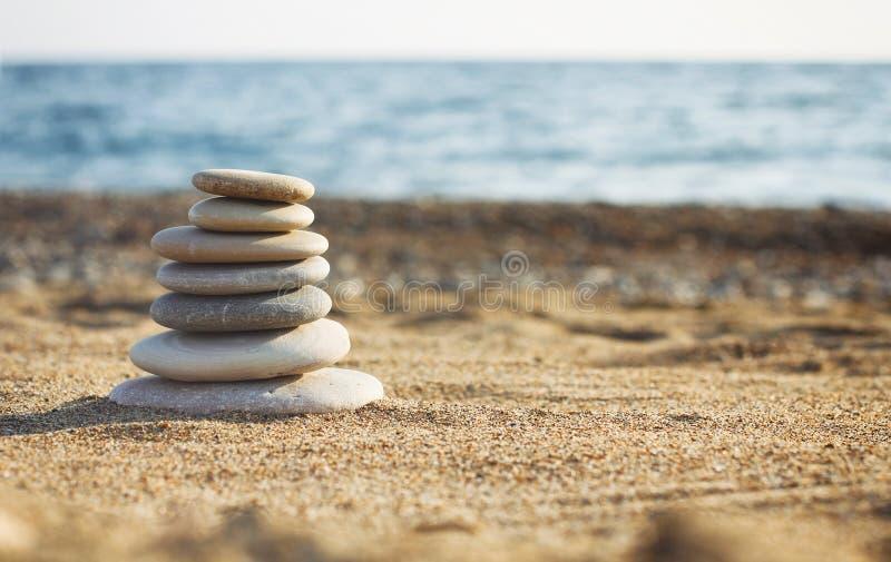 温泉石头禅宗金字塔在被弄脏的海背景的 在海滩的沙子 海岸 水波纹理 照片的左边 Pla 免版税图库摄影