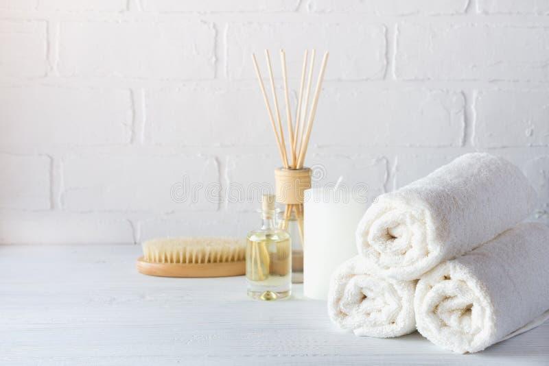 温泉芳香疗法背景 与白色毛巾,沭浴油,按摩刷子的静物画 库存图片