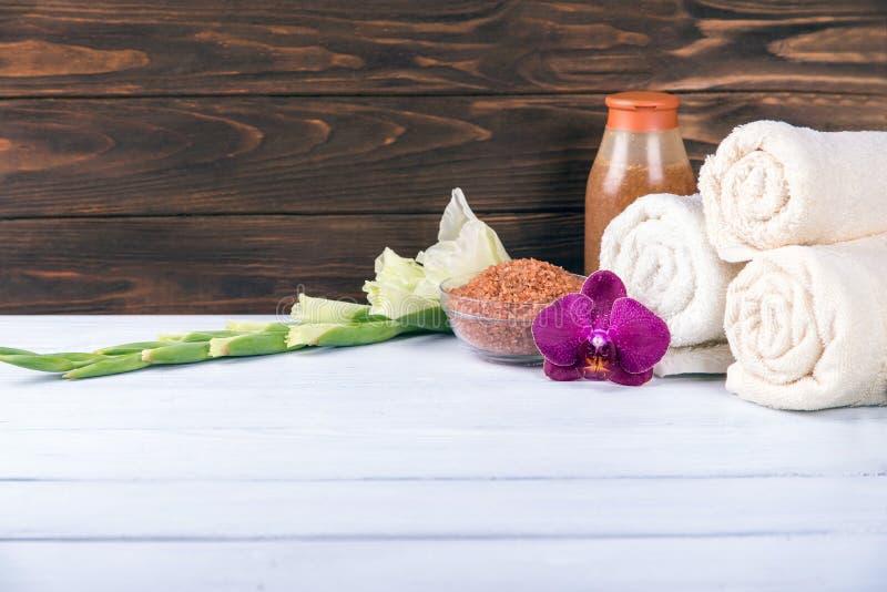 温泉设置与毛巾,洗刷和海盐与兰花在中心在白色木桌上 复制空间 免版税库存图片