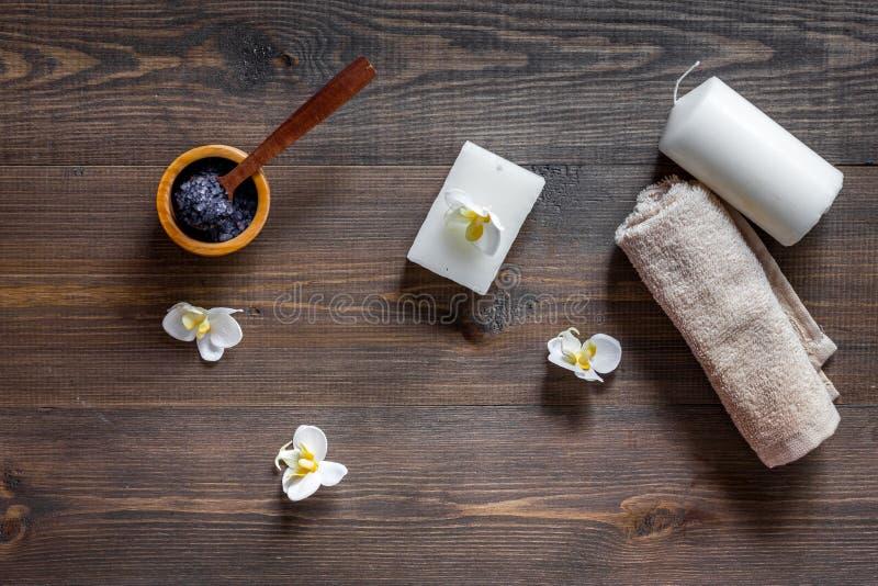 温泉设置了与盐、花和蜡烛在木桌背景顶视图 免版税库存图片
