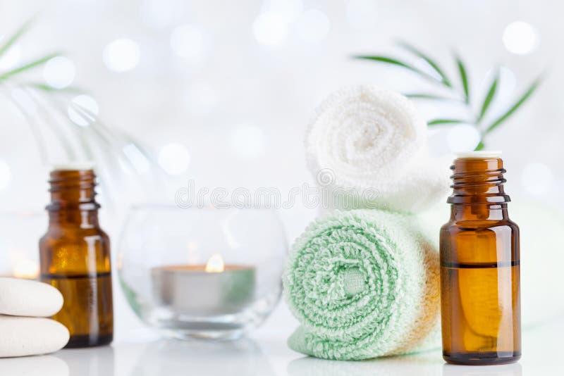 温泉,芳香疗法,健康,秀丽背景 精油瓶、毛巾和蜡烛在白色桌上 免版税库存图片