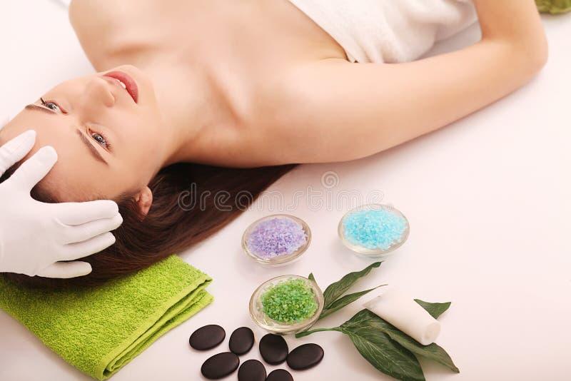 温泉 关心脸面护理 秀丽少妇得到在沙龙的顶头按摩 免版税库存照片