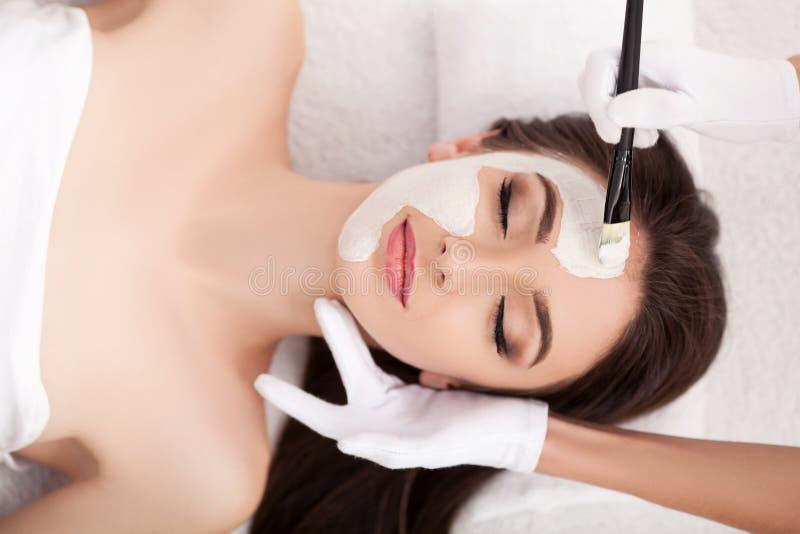 温泉 有黏土面具的可爱的滑稽的妇女在她的面孔 免版税图库摄影