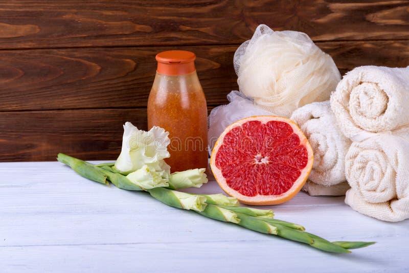 温泉治疗的构成在白色木背景的用葡萄柚、剑兰、毛巾、海绵和蜡烛 复制空间 免版税图库摄影