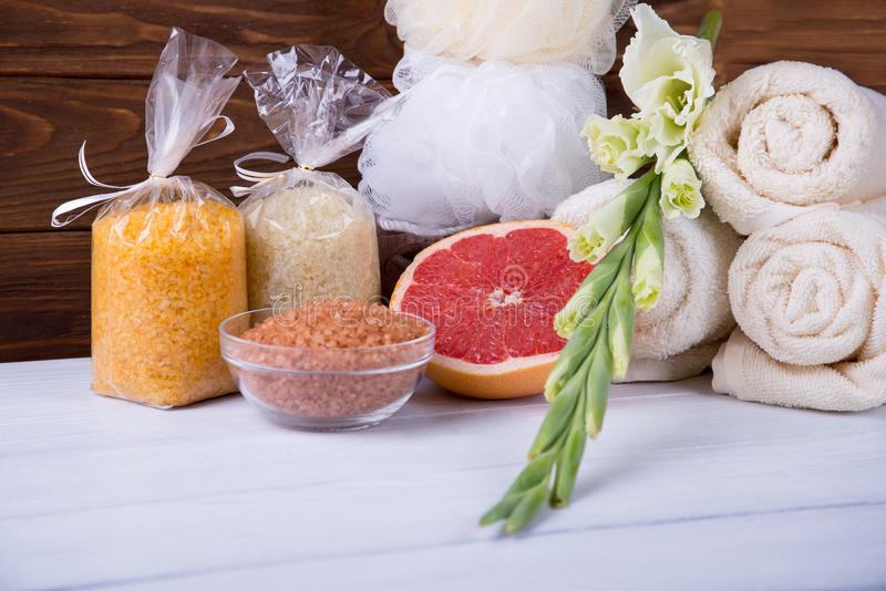 温泉治疗的构成在白色木背景的用葡萄柚、剑兰、毛巾、浴炸弹和蜡烛 拷贝spac 免版税图库摄影