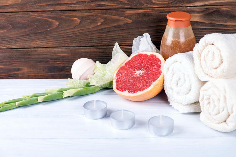 温泉治疗的构成在白色木背景的用葡萄柚、剑兰、毛巾、浴炸弹和蜡烛 拷贝spac 免版税库存照片
