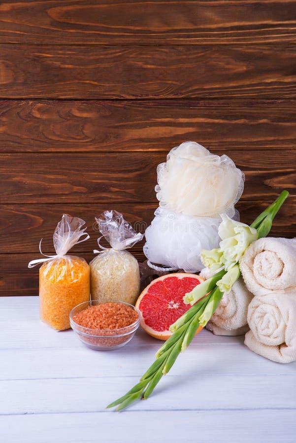 温泉治疗的构成在白色木背景的用葡萄柚、剑兰、毛巾、浴炸弹和蜡烛 拷贝spac 库存图片