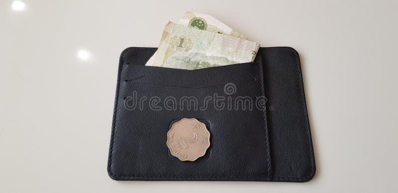 港元在有一元钞票的黑皮革钱包铸造放置 库存图片