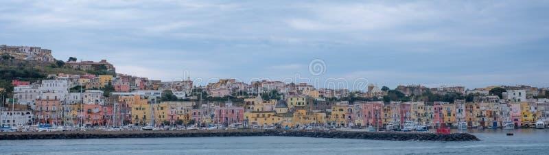 港口前面的全景照片与淡色房子的在普罗奇达意大利海岛上,拍摄从水 免版税图库摄影