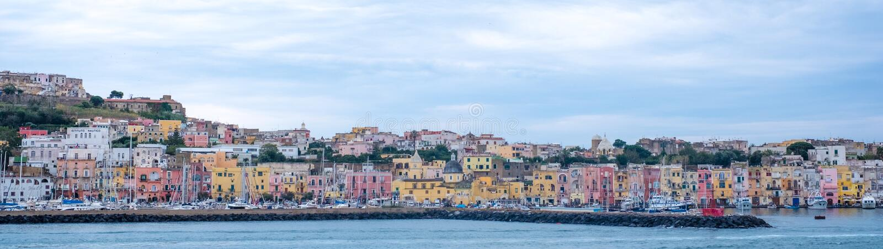 港口前面的全景照片与淡色房子的在普罗奇达意大利海岛上,拍摄从水 免版税库存图片
