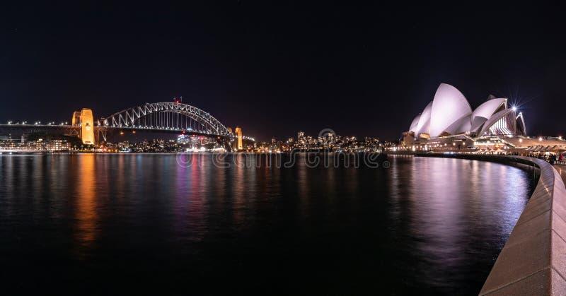 港口有五颜六色的城市的桥梁和歌剧院美妙的夜视图在悉尼,澳大利亚 图库摄影
