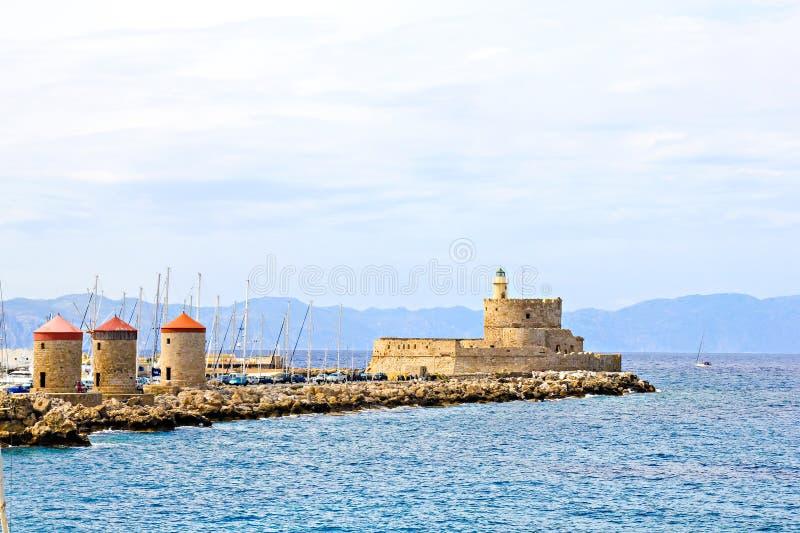 港口风车和灯塔圣尼古拉斯,罗得岛 免版税图库摄影