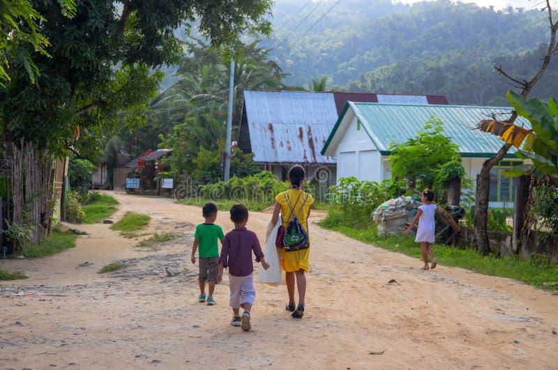 港巴顿,菲律宾- 2018年11月23日:妇女和孩子多灰尘的路的 在土气村庄街道上的Filippino家庭 库存图片