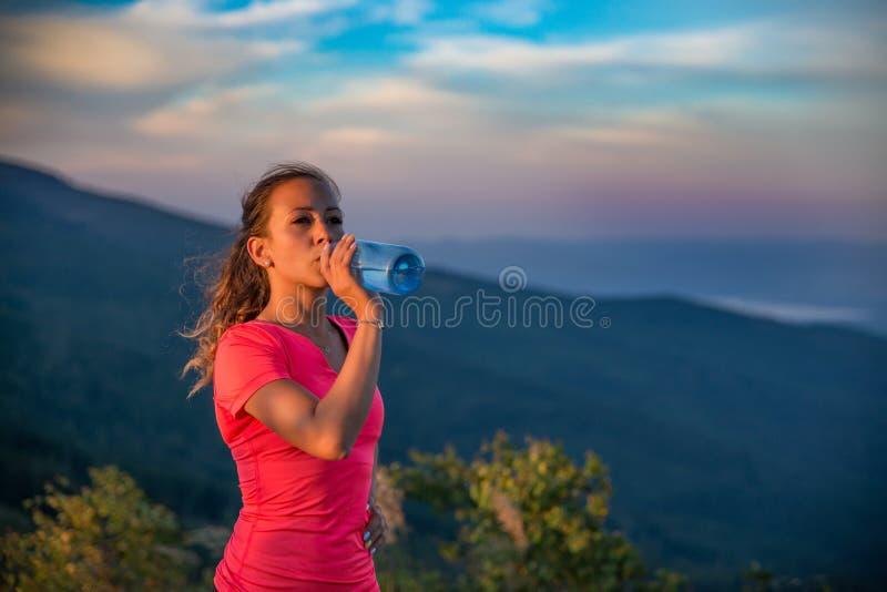渴从水瓶的妇女足迹赛跑者饮用水 免版税图库摄影