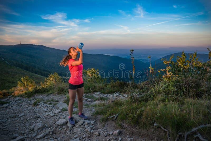 渴从水瓶的妇女足迹赛跑者饮用水 免版税库存图片