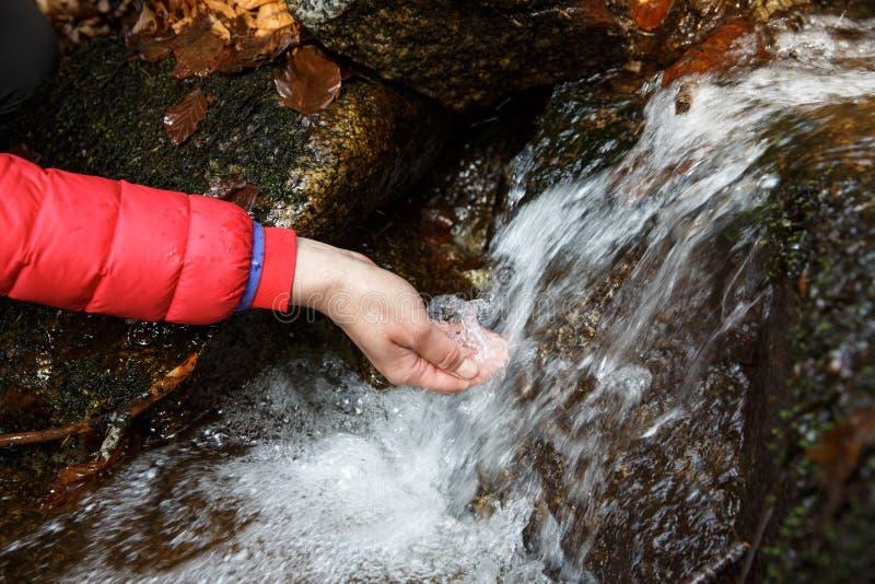 渴从透明的春天的远足者饮用水 免版税库存图片