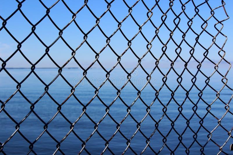 渴望以久的自由的概念性图象看与操刀任意打破在边的金属对开阔水域以远 库存图片