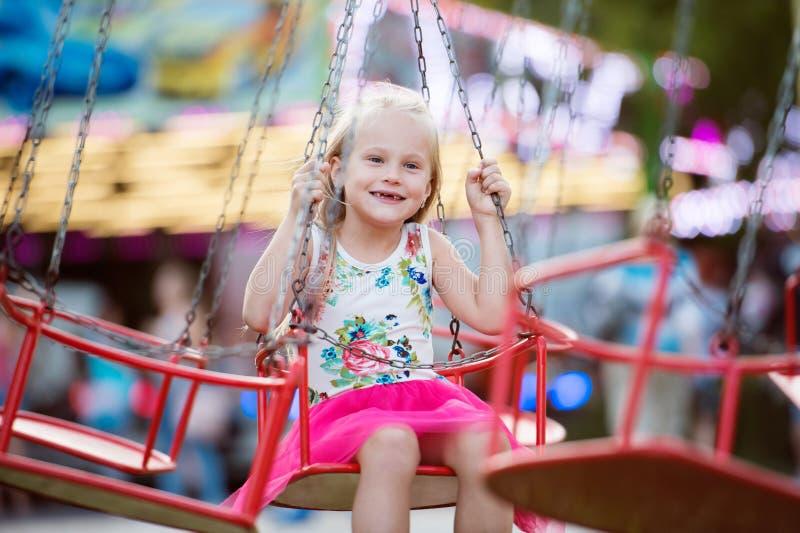 游乐园的,链摇摆乘驾逗人喜爱的小女孩 免版税库存照片