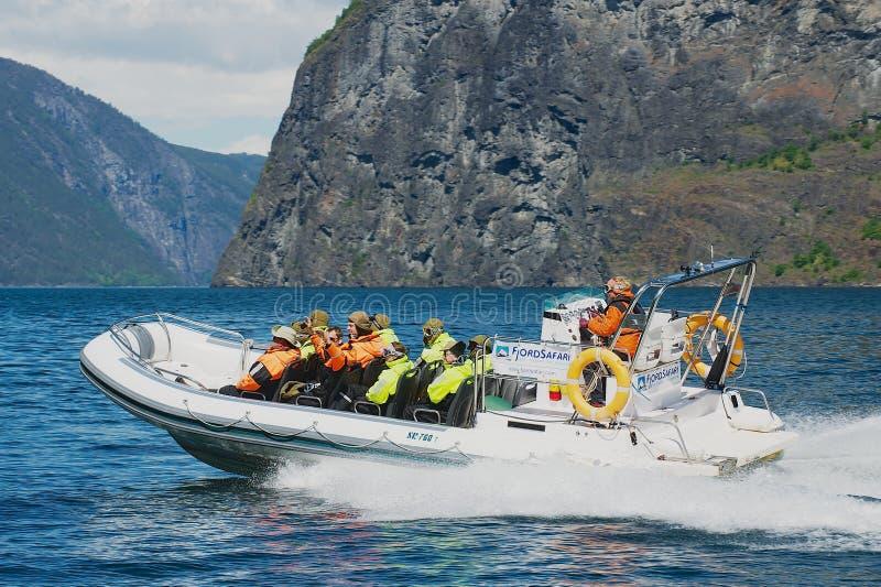 游人乘速度小船享受徒步旅行队游览在Aurlandsfjord在Flam,挪威 免版税库存图片