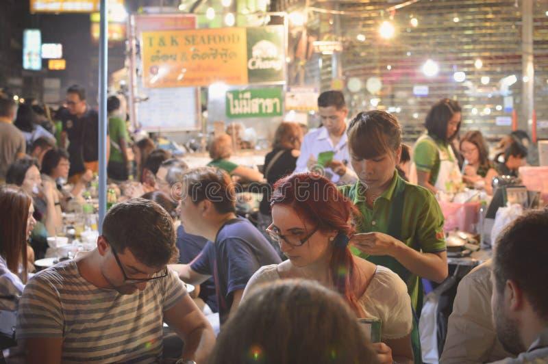 游人享用街道食物在夜市场上在唐人街, 免版税库存图片