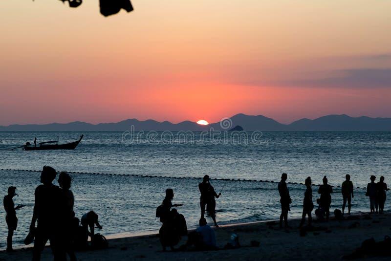 游人享用设置在山的壮观的日落太阳 海在前景 热带沙滩 免版税库存照片