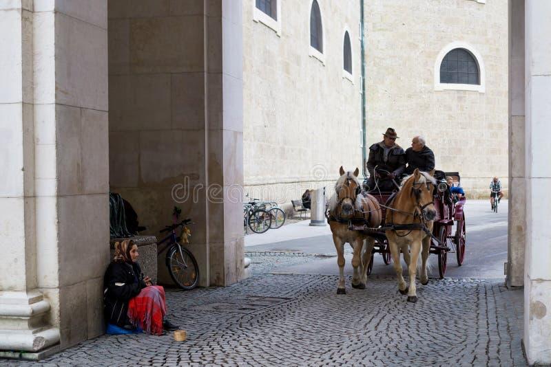 游人作为马支架乘驾老镇在萨尔茨堡,奥地利 免版税库存图片