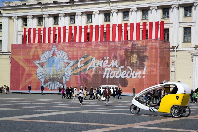 游人和一巨大的横幅`愉快的胜利天`在宫殿在圣彼德堡摆正 免版税图库摄影