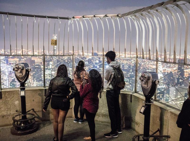 游人和双筒望远镜在帝国大厦顶部在晚上 免版税图库摄影
