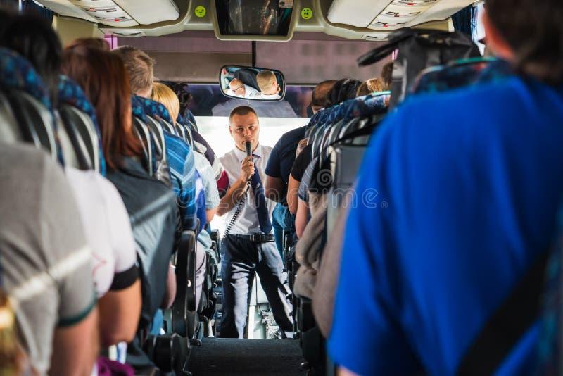 游人和男性导游与一个话筒在公共汽车上 免版税图库摄影