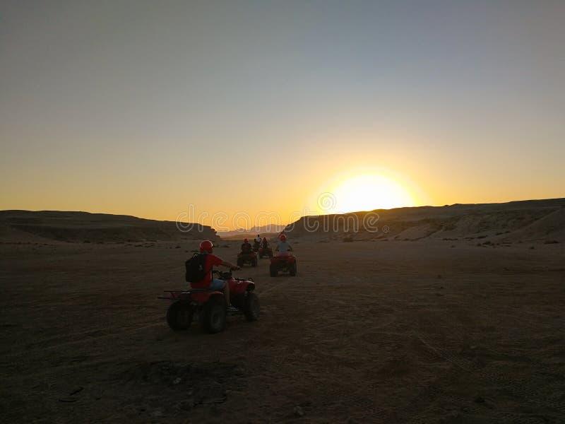 游人在一辆方形字体自行车乘坐在沙漠在日落 免版税库存照片