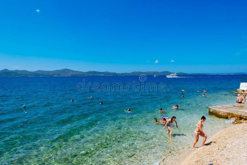 游人在亚得里亚海游泳在扎达尔附近在晴天 免版税库存图片