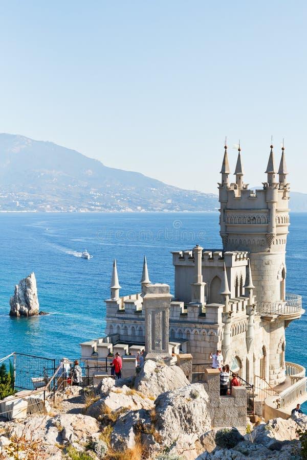 游人在克里米亚临近燕子的巢城堡 免版税库存照片