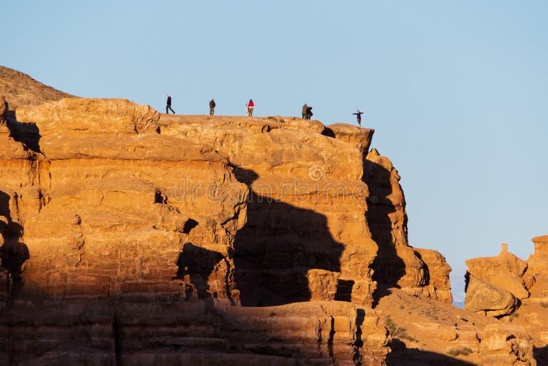 游人在哈萨克斯坦走并且拍在Charyn峡谷背景的照片  免版税库存照片